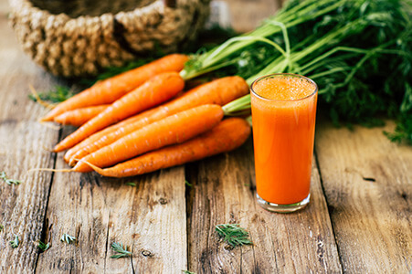 Carrot Juice with Fresh Carrots on Table