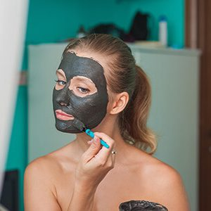 Woman Applying Clay Mask